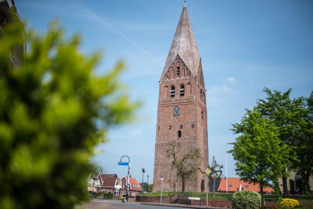 Kerktoren uit 1289 op het kerkplein van een dorpje in Groningen