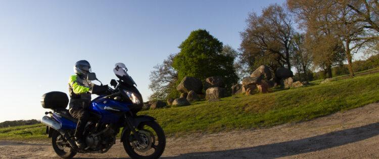 Motorrijder rijdt voor een hunnebed in Drenthe langs