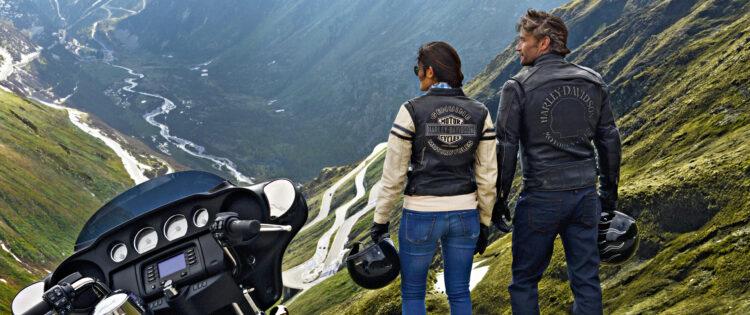 Een motor en twee motorrijders die uitkijken over de bochten in de Zwitserse Alpen