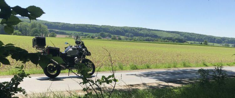 Een uitzicht over het Teutoburgerwald met op de voorgrond een motor geparkeerd op de weg