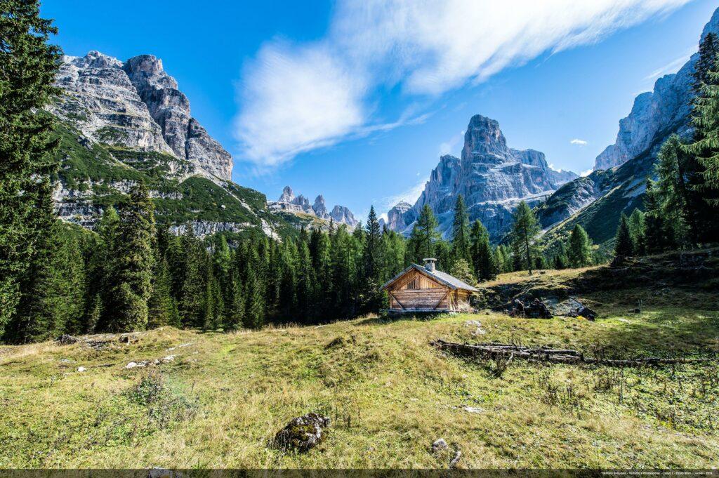 Uitzicht over een berghut tussen de bossen en bergtoppen in Trentiono, Italie