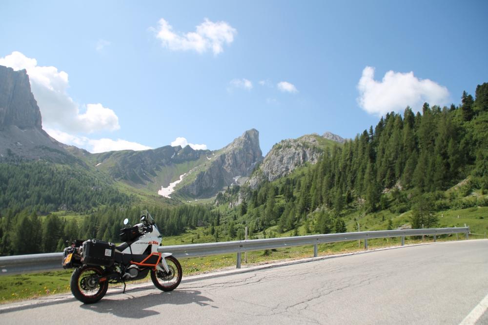 Een geparkeerde motor langs de vangrail met de bergen van de Dolomieten op de achtergrond