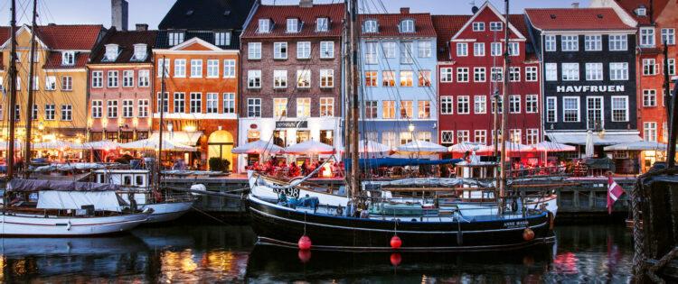 Uitzicht in de avond over de haven van Kopenhagen in Denemarken met zeilboten en kleurrijke huizen