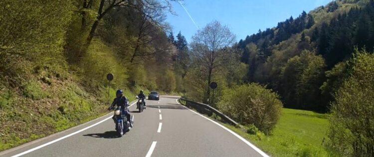 Twee motorrijders rijden op een zonnige dag door de heuvels van Luxemburg